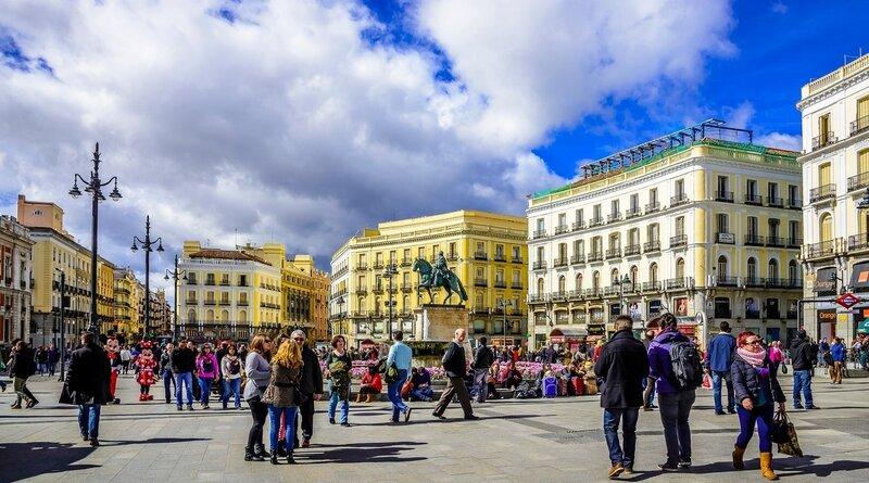 С площади Пуэрта-дель-Соль начинаются исчисление расстояний в Испании, нулевой километр. Выглядит она как просто очень широкая улица. Самое приметное строение на площади — красно-белое здание правительства Мадрида с высокой металлической беседкой над башней с часами Рамона Лосада.