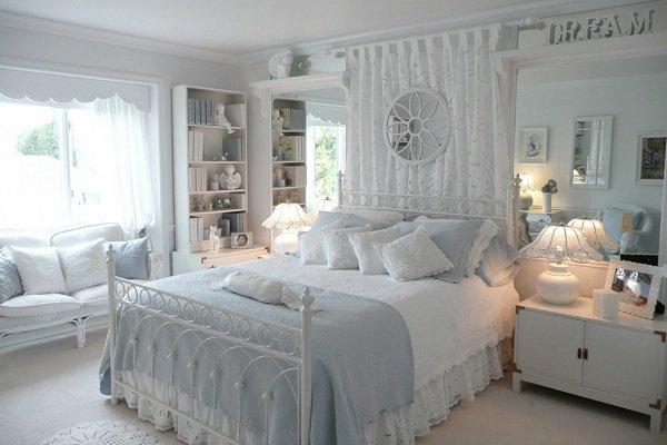 Кровать с белыми кованными спинками в интерьере голубой спальни