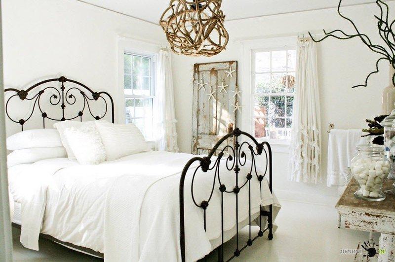 Кровать с черными кованными спинками в интерьере белой спальни в стиле шебби шик