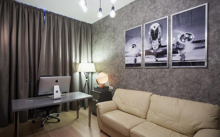 Рабочий кабинет выглядит как уютная гостиная. Интерьер выдержан в комфортной серо-бежевой гамме, с элегантной мебелью, драпировками и разнообразным светом, включающим торшер, настольную лампу и люстру.