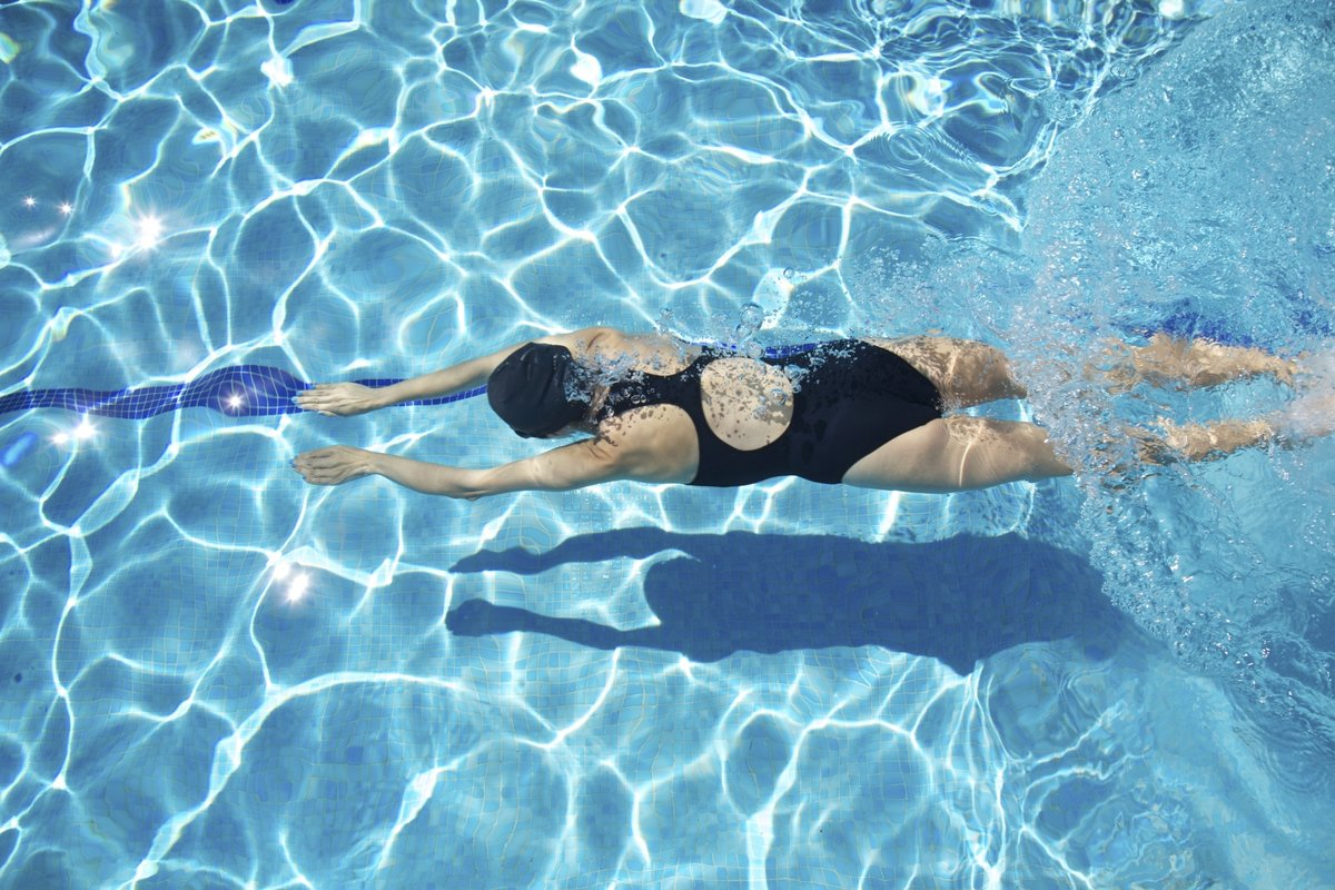 девушка плавает в черном купальнике