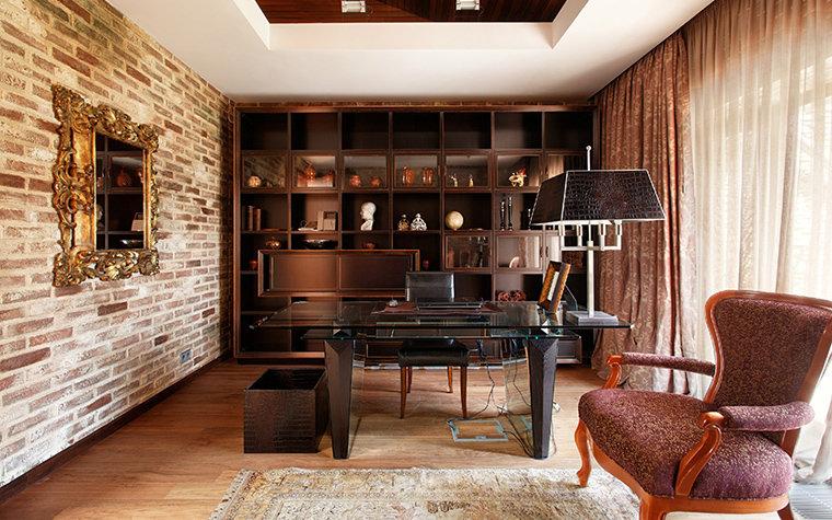 Брутальная кирпичная отделка стены противоположной большому окну, плотные шторы и мебель в темных тонах.