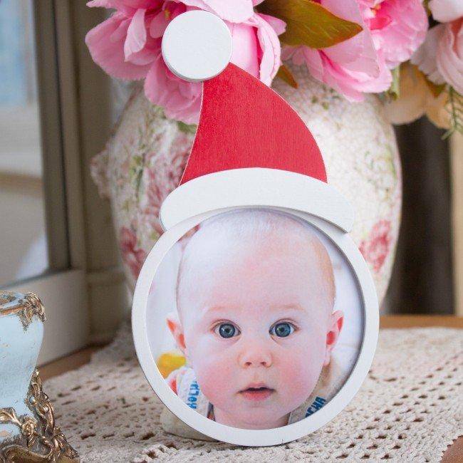 Необычная детская деревянная фоторамка в рождественском стиле. Круглая остекленная фоторамка из фанеры дополнена колпаком Санты, изделие выполнено в традиционной красно-белой цветовой гамме. В задней части фоторамки предусмотрена крышка для легкой смены фото.
