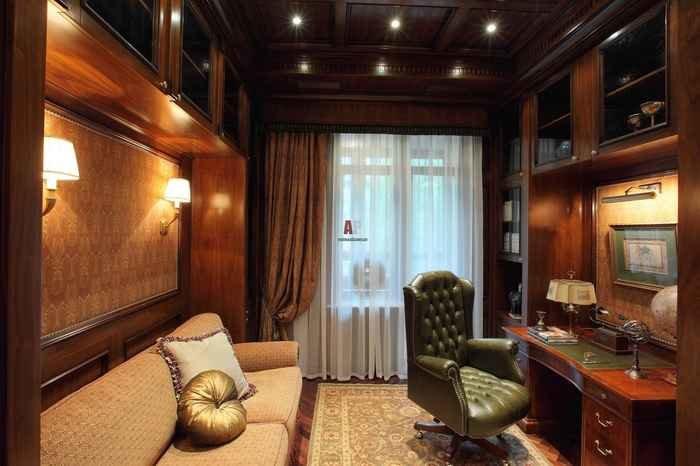 Потолок, стены и письменный стол из темного натурального дерева, удобное темно-зеленое кресло.