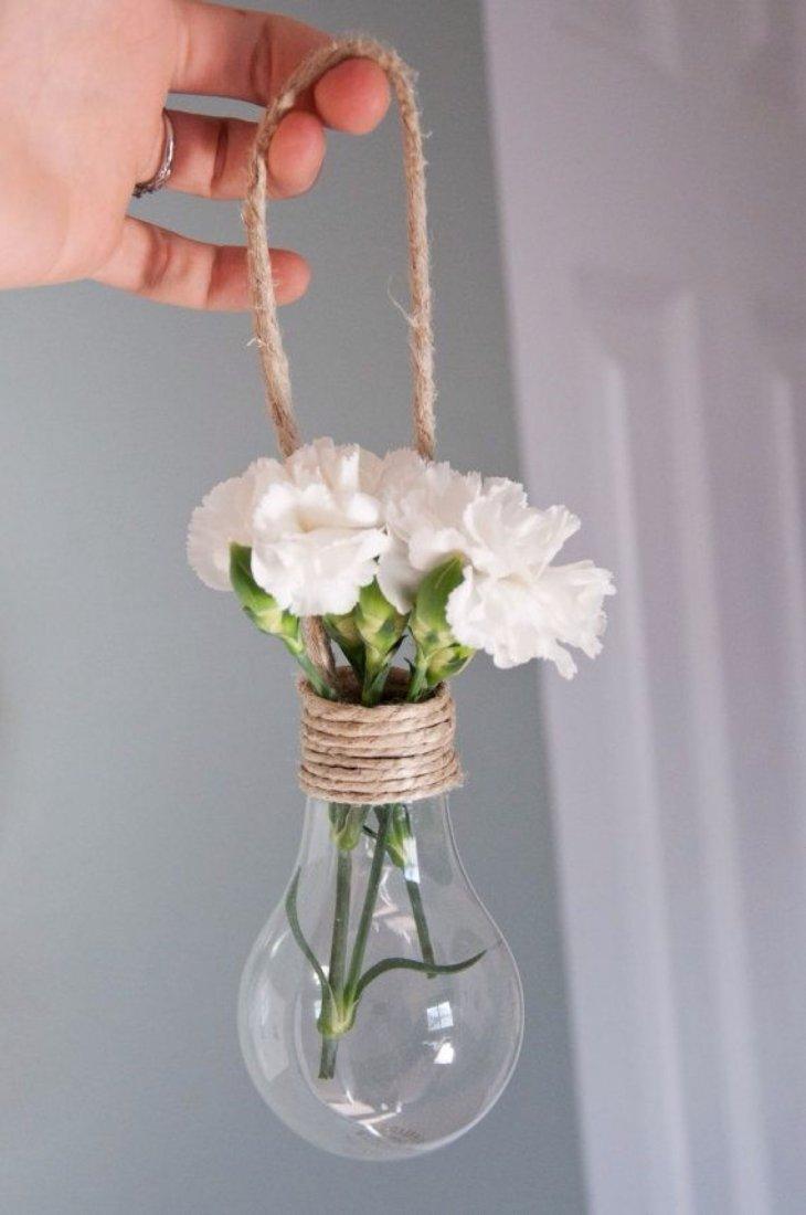 Не спешите выкидывать отслужившую свой срок лампу накаливания. Ее можно использовать в качестве оригинальной вазы для срезанных цветов или наполнить грунтом и посадить в нее зелень. Самое сложное в этом деле – вынуть внутреннюю часть лампочки.
