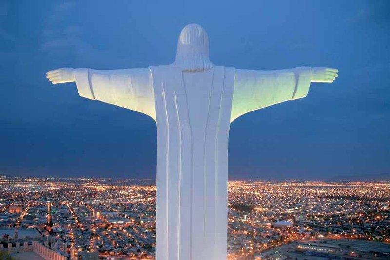 татуя Христа с раскинутыми руками обращена на вечерний город Торреон, штат Коауила, Мексика