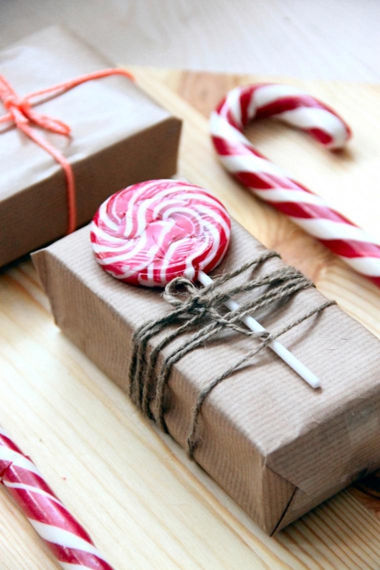 упакованный бумагой подарок с привазанной серой веревкой конфетой на палочке