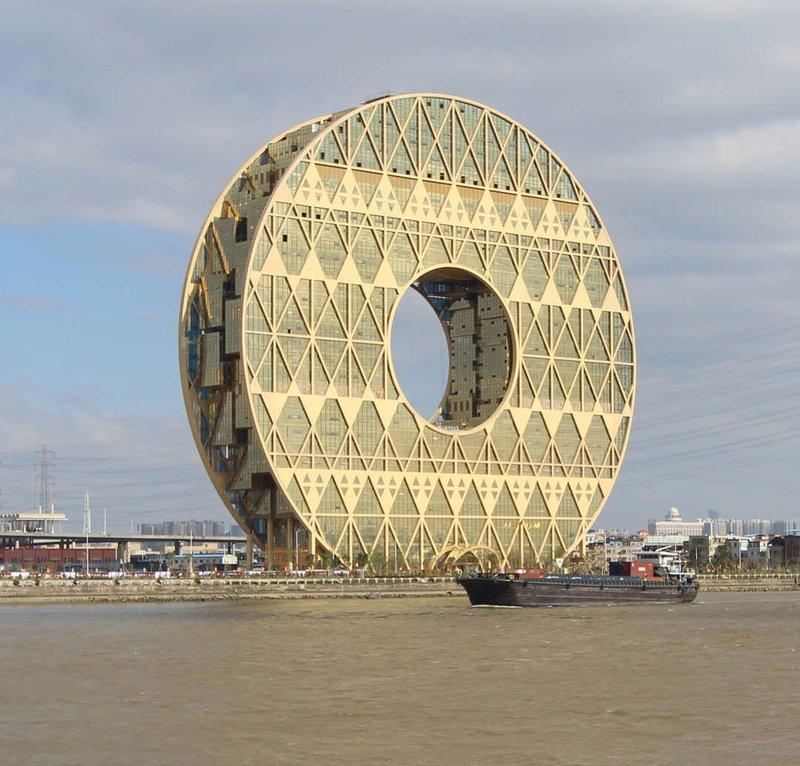 """33-этажное здание высотой 138 м было построено в 2013 году в Гуанчжоу по проекту итальянца Джузеппе Ди Паскуале. В центре """"Круга"""" расположено круглое отверстие диаметром около 50 м. При отражении здания в реке получается изображение, похожее на цифру 8, которая считается у китайцев счастливой. Гуанчжоуский комплекс считается самым большим круглым зданием в мире."""