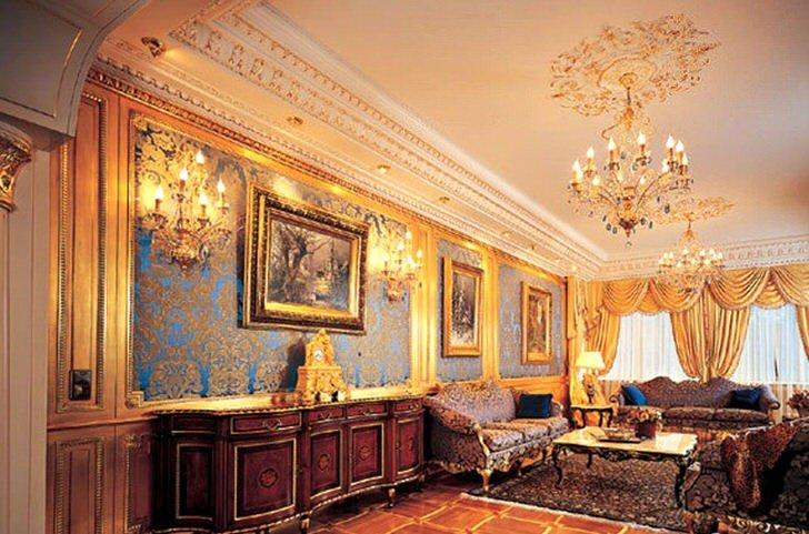 Гостиная в доме большой французской семьи. Стиль ампир в гостевой комнате демонстрирует статус хозяев дома. Королевские, дорогие апартаменты интересны правильным сочетанием деталей. Лепнина на стенах, светильники, люстра и ламбрекены золотого цвета гармонично смотрятся в общей картине интерьера.