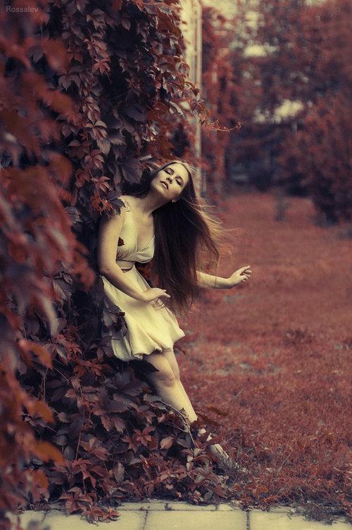 Девушка с длинными волосами с закрытыми глазами в белом платье стоит среди листьев дикого винограда.