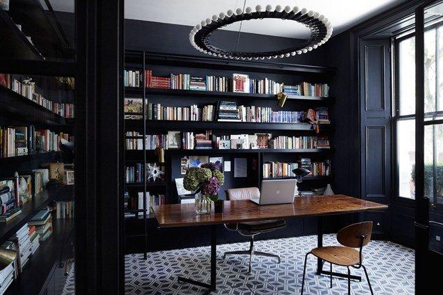 стены комнаты окрашены в матовый черный цвет, также дизайнеры использовали черную классическую мебель, которая отлично сочетается с белым потолком комнаты,  письменным столом и напольным орнаментом