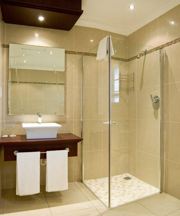 Дизайн маленькой ванной с плиткой и душевой кабиной