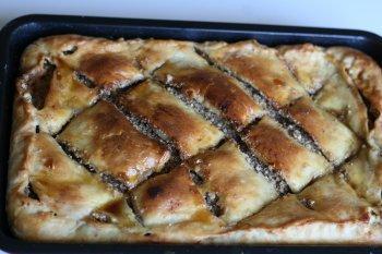 Приготовить дрожжевое безопарное тесто, раскатать тонким пластом. На тесто выложить начинку из орехов, сахара и кардамона, прокрученных через мясорубку. Сверху положить слой теста