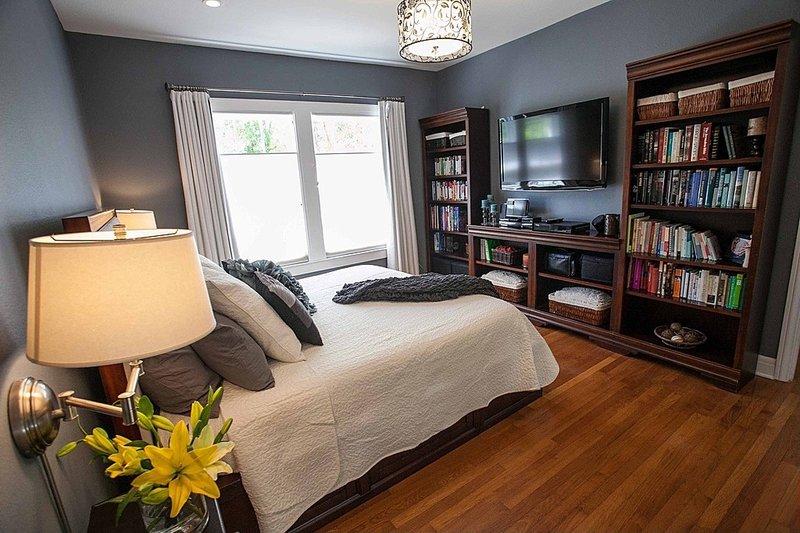 телевизор между книжными полками в спальне