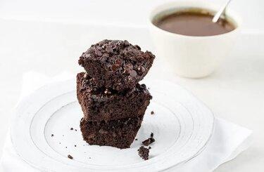 recept-karamelno---shokoladnykh-pirozhnykh-iz-kokosovoj-muki-na-belom-blyudce-pirozhnoe-korichnevogo-cveta