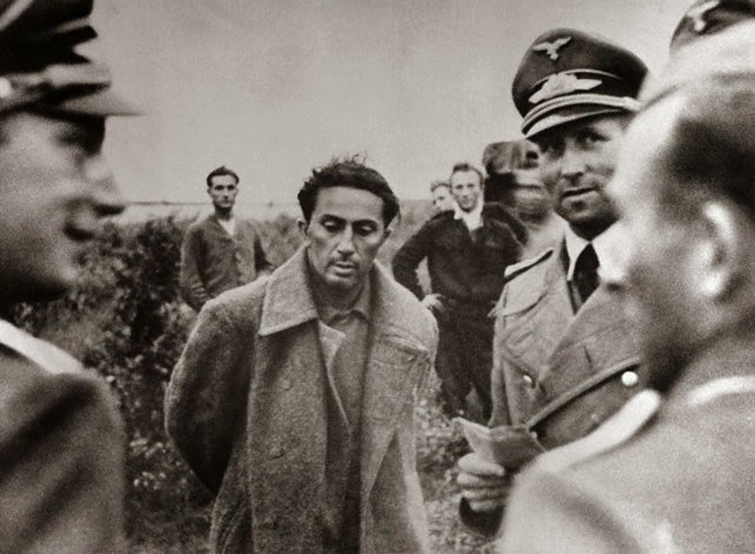 Это знаменитое фото - откровенная постановка. По официальной версии Яков Сталин попал в плен в гражданской одежде. А на этой фотографии он (точнее - тот, кто его изображает) в армейской шинели.