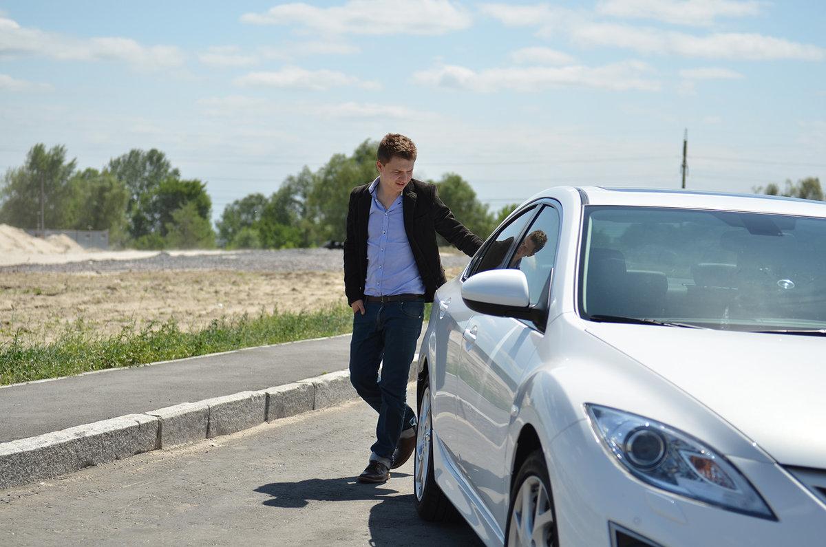 Парень стоящий возле машины
