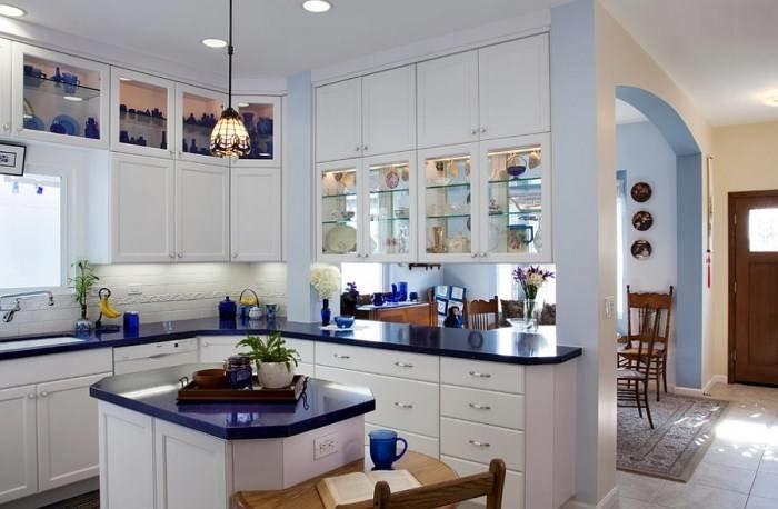 красивая белая кухня с небольшим островом, столешницами и посудой глубокого синего цвета