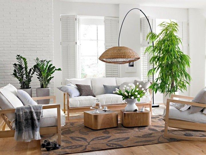 Растения в белой гостиной с плетеным дизайнерским торшером
