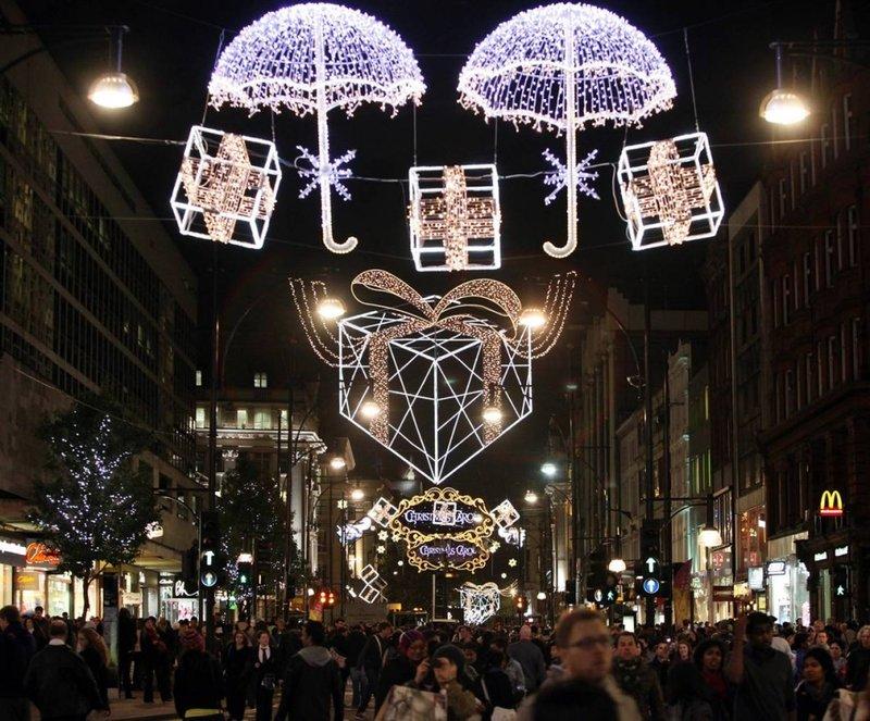 Прохожие идут под рождественскими гирляндами на Оксфорд Стрит вскоре после их официального включения 3 ноября в Лондоне. Две главные торговые улицы в Лондоне Вэст Энд на Оксфорд Стрит и Риджент Стрит были включены одновременно