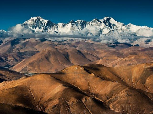 Покрытые снегом вершины высоких гор над плоскогорьем