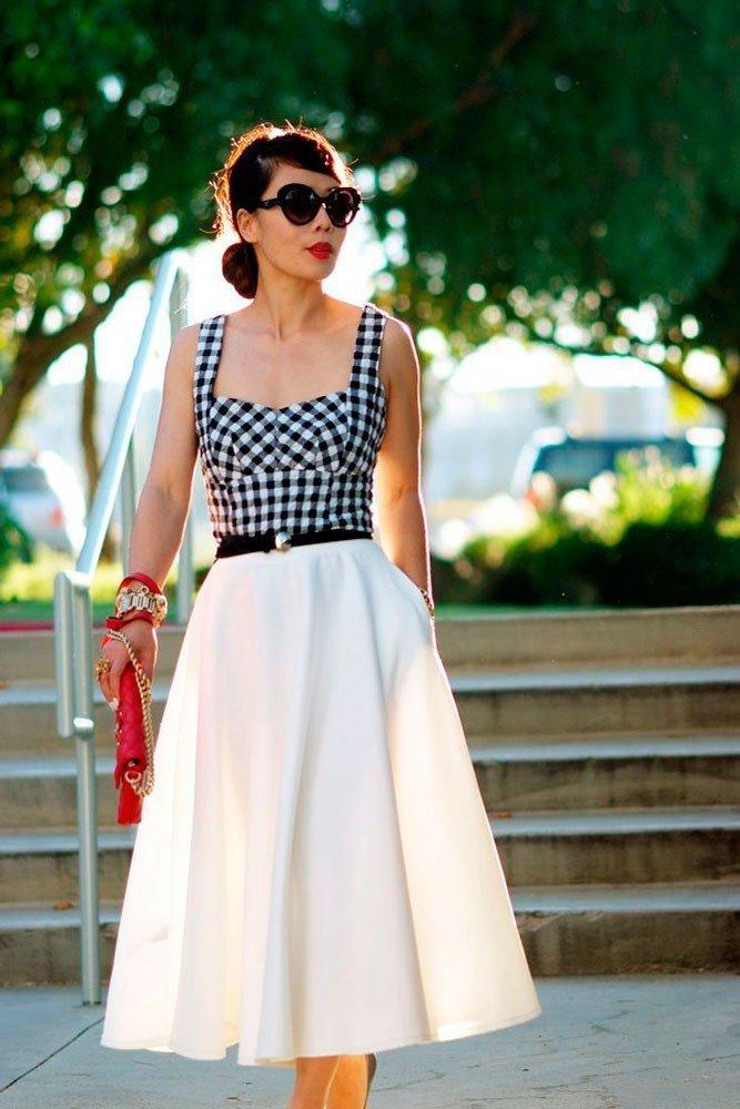 Девушка в длинной юбке миди белого цвета и топом в клетку