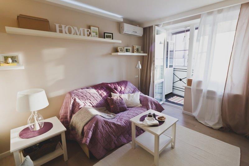 Расслабленная атмосфера в комнате создается за счет нежных кремовых тонов, мягкого текстиля и необычным аксессуарам: настенным полочкам с рамками для фотографий и красивым торшерам. Мебели в гостиной немного, но она очень романтичная. Разбавляет спокойную цветовую гамму сиреневое покрывало и яркие подушечки