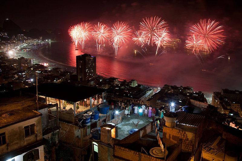 Жители трущобы Паван-Паванзину смотрят праздничный фейерверк по случаю Нового года на пляже Копакабана в Рио-де-Жанейро, Бразилия.