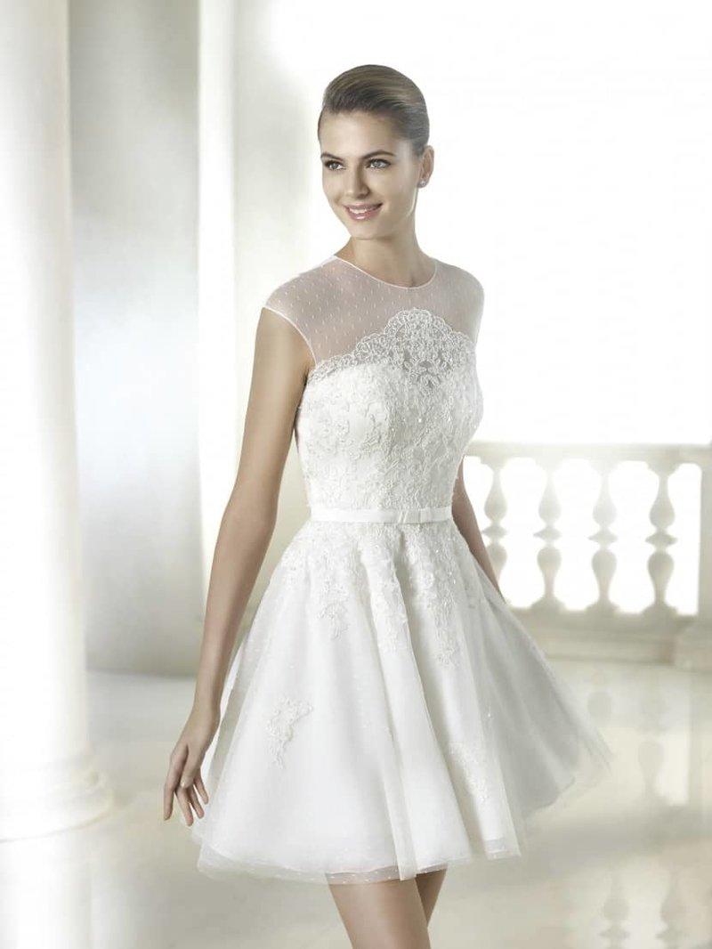 Короткое свадебное платье выглядит кокетливо и романтично. Пышная, воздушная юбка из легкого матового фатина длиной до середины бедра придает образу ретро-ноты. Поддерживает впечатление и полупрозрачная ткань в мелкий горошек, закрывающая область декольте.  Лиф и корсаж свадебного платья отделаны нежным мелким кружевом с цветочными мотивами и расшиты пайетками, кружево в виде аппликаций использовано и на юбке. Спинка платья украшена рядом декоративных пуговиц и полупрозрачной кружевной вставкой. Дополняет образ тонкий пояс с бантиком, который при желании можно снять.  Свадебное платье из коллекции 2015 года
