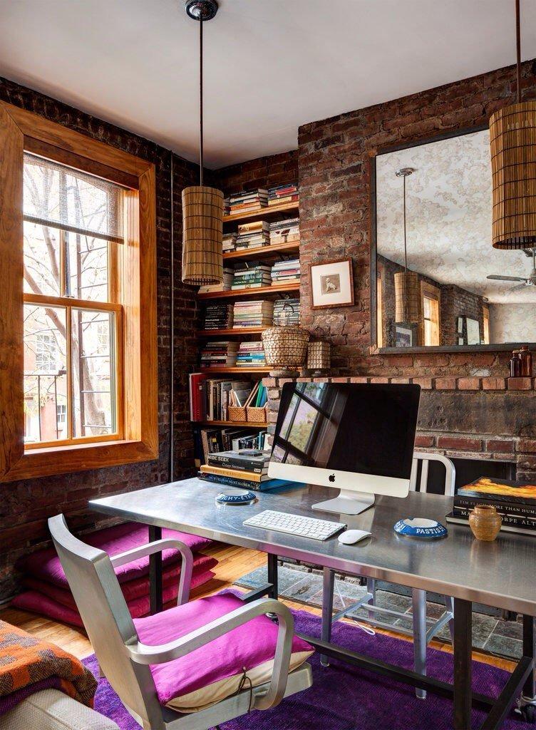 Яркие женственные цвета сочетаются с кирпичной стеной и спокойным тоном деревянного пола. Солнечный свет отражается от металлической столешницы, придавая этому эклектичному рабочему пространству еще большую объемность.