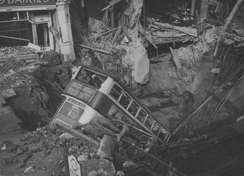 Двухэтажный автобус в бомбовой воронке у станции лондонского метро «Белхэм» после налета немецкой авиации [2]