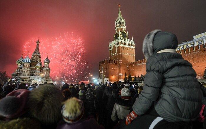 Москвичи и гости столицы, встречающие Новый год на Красной Площади, наблюдают праздничный салют.