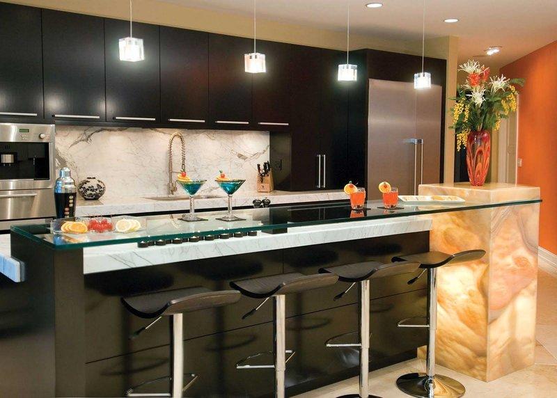 Если расположение стола в середине, то лучше осветите его люстрой с параметром регулирования мощности и изменяемым от потолка расстоянием. Светильник настраивают в зависимости от условий: обед, завтрак, ужин, гостевой прием, выполнение домашних работ. Для расположенного в центре большого стола, установите настольный светильник. Если стол находится у стены, то лучше использовать светильники настенные, их разновидностей очень и очень много, нужно только выбрать.