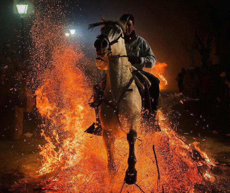 Всадник на лошади проезжает через костер
