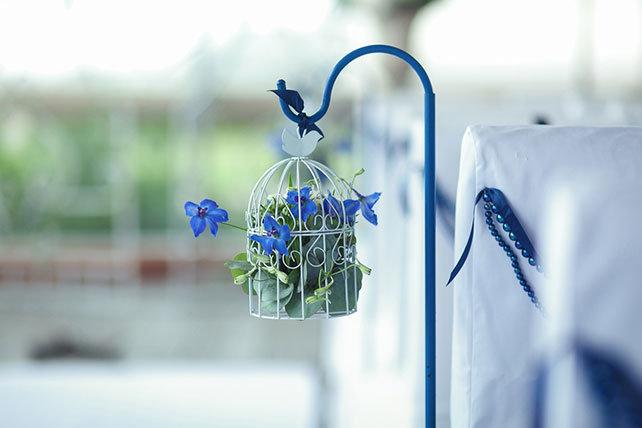 Элегантная черничная свадьба, декор места торжества ажурными клетками с цветами