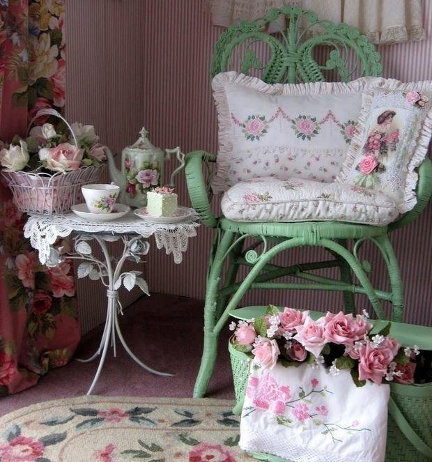 Зеленый плетеный стул и белый столик на ножках в виде роз