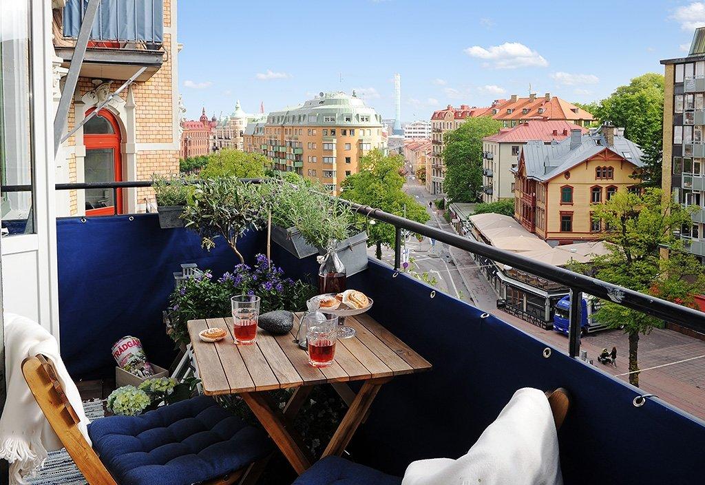 """Уютный балкон с синими перилами и сидениями кресел"""" - карточ."""