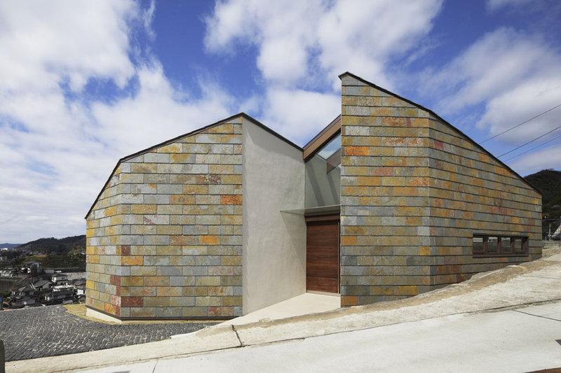 Расположенный на холме многогранный дом, стены и крыша которого отделаны натуральным камнем с песочными оттенками, очаровывает своим одновременно строгим и по-деревенски доброжелательным видом.