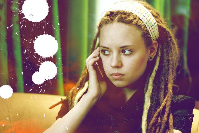 Фото Серьезная девушка с дредами, разговаривает по телефону.