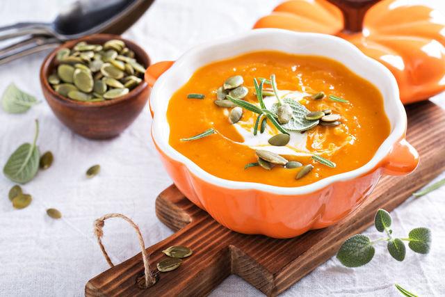 Тарелки с супом украшаем ложкой сметаны и тыквенными семечками