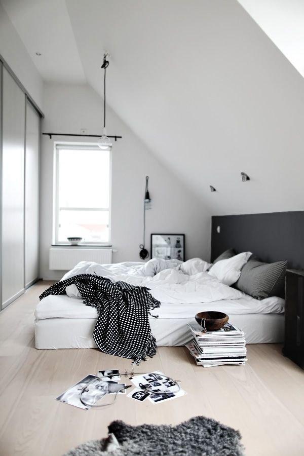 Наклонный потолок даёт идеальную возможность оформить одну стену полностью чёрным цветом, при этом не «утяжеляя» общее пространство. Стена является логическим продолжением чёрного изголовья кровати.