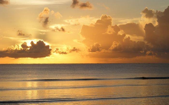 Тучи закрывающие восходящее солнце над морем.