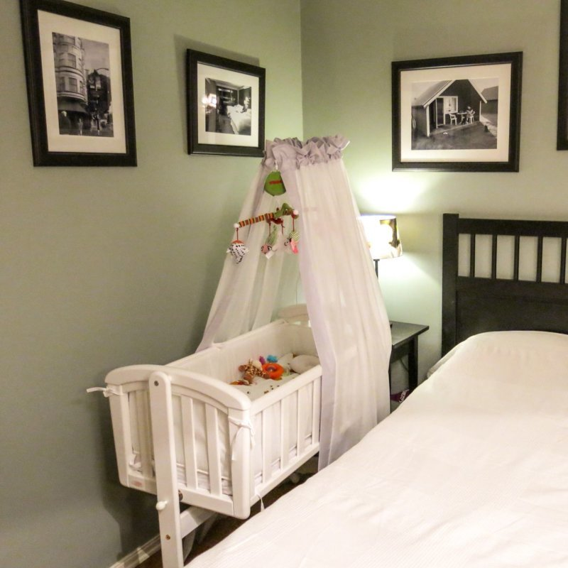 Детская люлька с балдахином возле кровати родителей.