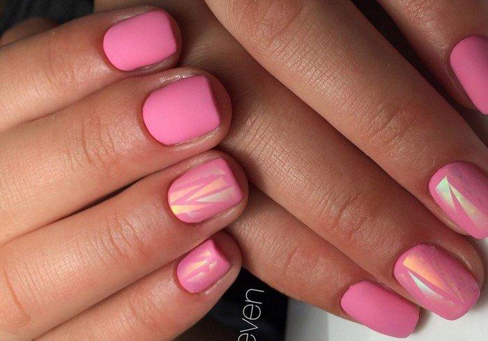 Аккуратность и красоту коротких ногтей квадратной формы выгодно подчеркнёт матовый розовый маникюр с перламутровым геометрическим дизайном на отдельных ногтях.