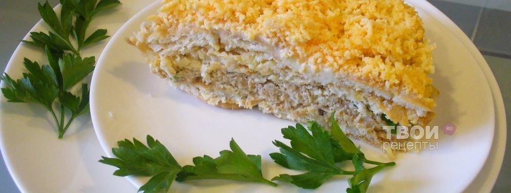 Накрываем рыбный слой крекером, сыр трём на крупной тёрке, чеснок на мелкой, смешиваем с небольшим количеством майонеза и распределяем равномерно:.