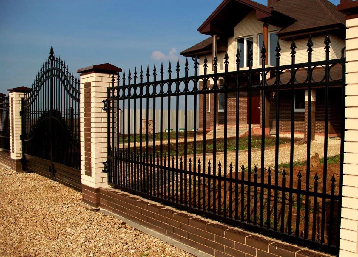 Металлический забор решеткой черный на фоне дома  кирпичного