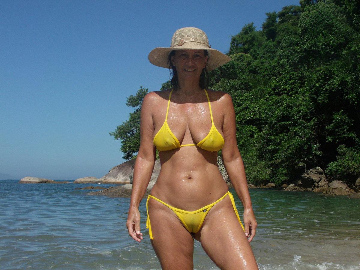 Жена на пляже в бикини частное, катается на велосипеде со страпоном