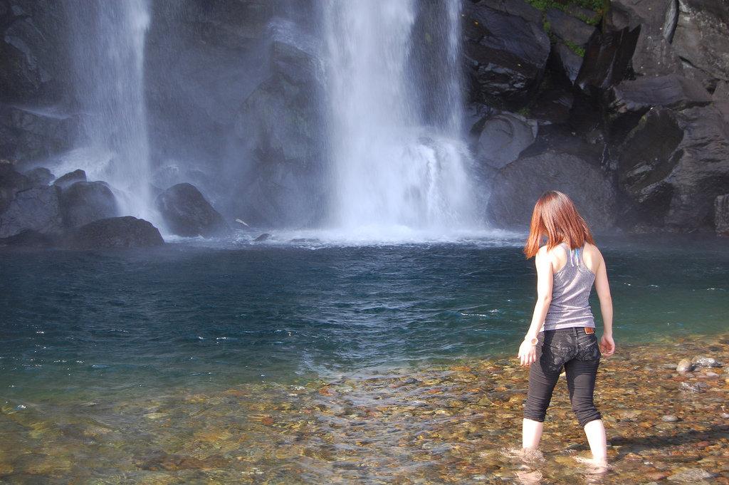 рыжая девушка возле водопада дразняще
