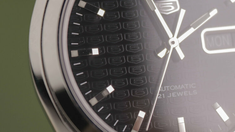 On the dial of the watch there is a pattern with the corporate logo Seiko 5